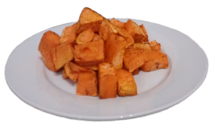 Photograph of roasted sweet potato chunks on a white plate