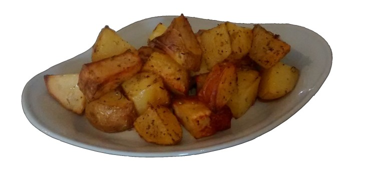 A photograph of roast potato chunks on a blue-grey plate