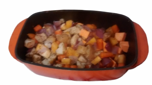 Photograph of an orange oven dish filled with chopped carrot, onion, potato, swede, parsnip, and sweet potato, lightly coated in herbs and oil