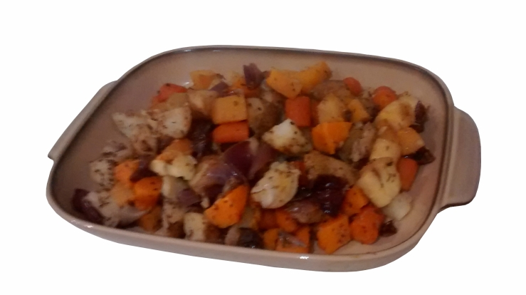 Photograph of a brown serving dish filled with roasted carrot, onion, potato, swede, parsnip, and sweet potato