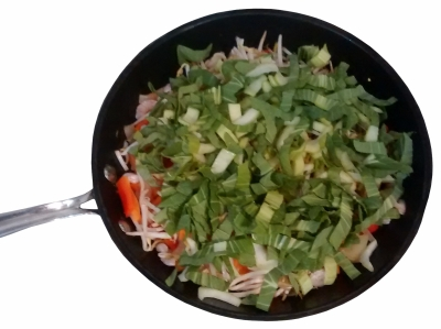 Photograph of a wok with a layer of pak choi on top of beansprouts, prawns, red pepper, carrots & onions