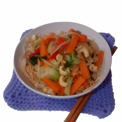 Photograph of white bowl filled with stir-fried vegetables and cashew nuts on egg noodles