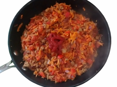 Photograph of a wok containing mixed vegetables and mince, with a roughly tablespoon-sized dollop of tomato puree on top