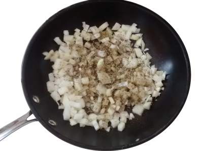 Photograph of a wok containing diced white onion and mixed herbs
