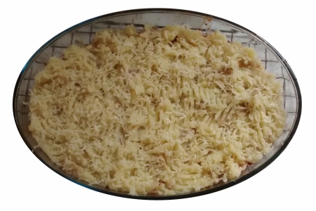 Photograph of an oval glass dish filled with a layer of mashed potato, topped with grated cheese