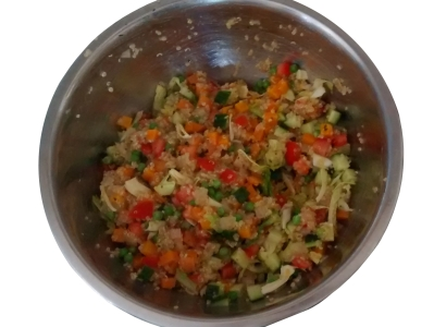 Photograph of a large mixing bowl containing quinoa, peas, diced carrot, tomato, and cucumber