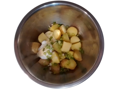 Photograph of a mixing bowl containing cooked potato chunks, sliced spring onion, and a spoonful each of mayonnaise and salad cream