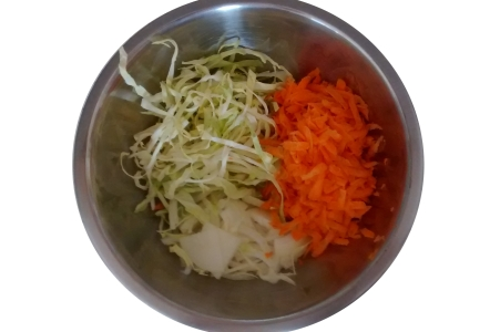 Photograph of thinly sliced cabbage and white onion, and grated carrot in a stainless steel mixing bowl