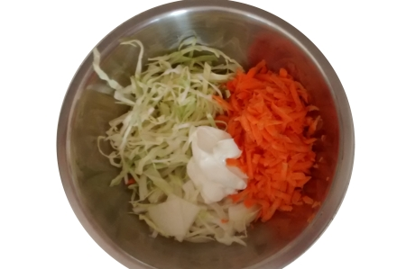 Photograph of thinly sliced cabbage and white onion, grated carrot, two large dollops of mayonnaise and a splash of vinegar in a stainless steel mixing bowl