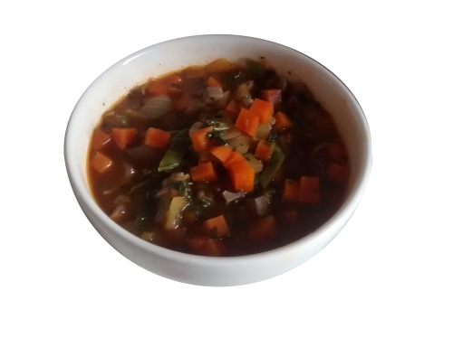 Photograph of a white bowl full of soup