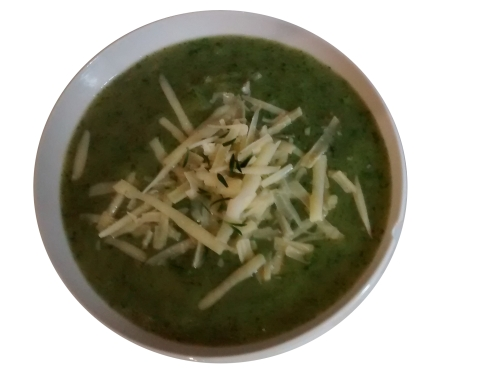 Photograph of a white bowl filled with green soup, topped with grated cheese and thyme