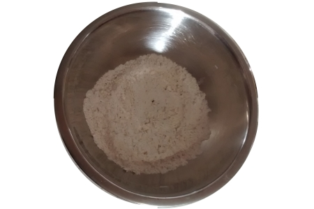 Photograph of a mixing bowl filled with flour, with small amounts of dried herbs visible