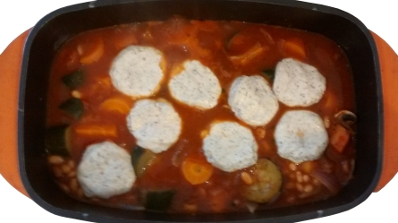Photograph of eight pale, round dumplings floating on a red casserole
