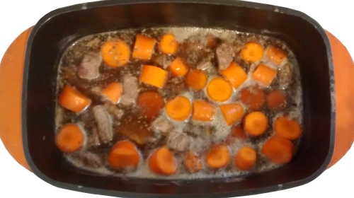 Photograph of a casserole dish filled with chunks of carrot and meat, and beer