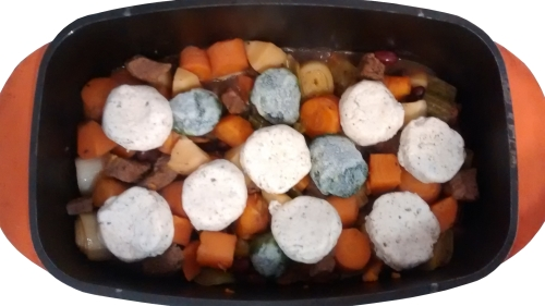 Photograph of a casserole dish filled with chunks of meat and vegetables, topped with balls of frozen spinach, and dumplings